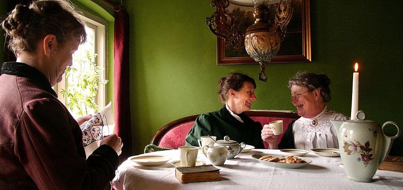 1910 : Sønderjysk kaffebord i Als hvor Lærerinde Frøken Ludvigsen (tv) er hjemvendt fra Aabenraa og beretter nyt til Fyrbøderfrue Møller og Boghandlerfrue Johansen om kvindernes emancipering (frigørelse og ligestilling). På grund af tyskernes belejring må der kun undervises i tysk i skolerne i det sønderjyske, ligesom danske sange ikke måtte kunne høres udenfor. Ved kaffebordet nyder man derfor jødekager der er bagt i det nymodens støbejernskomfur og slutter hyggen med en dansk sang fra højskolesangbogen. Lærerinde Frøken Ludvigsen underviser i dansk historie og dansk sprog privat. Fyrbøderfrue Møller underviser i klaver i hjemmet imens Boghandlerfruen står for husførelsen hjemme.